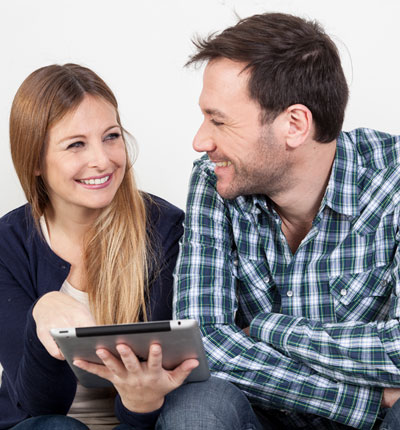 Couple smiling at eat other, which girl holds a iPad